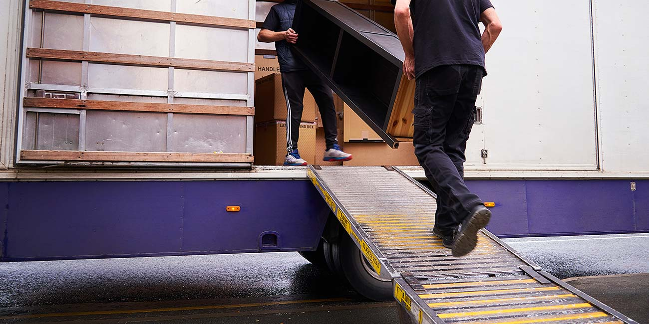 Movers carrying furniture into the truck